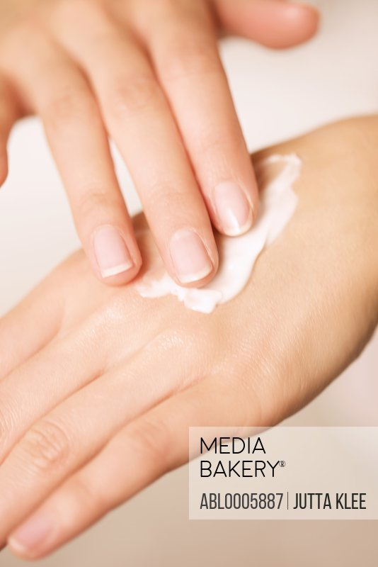 Extreme close up of a woman's hands applying hand lotion