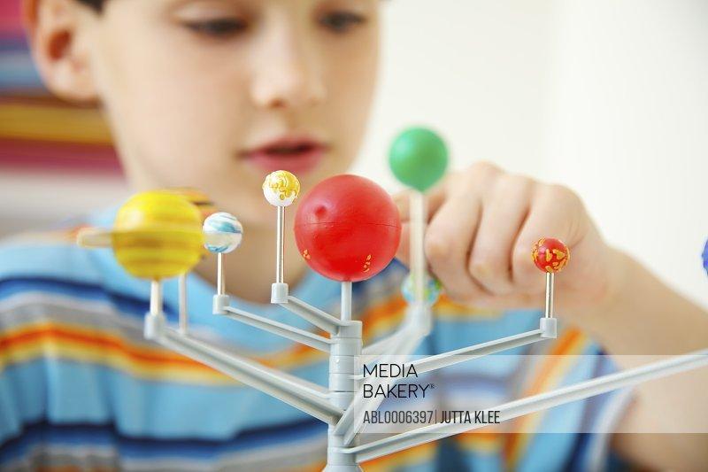 Boy Inspecting Solar System Model