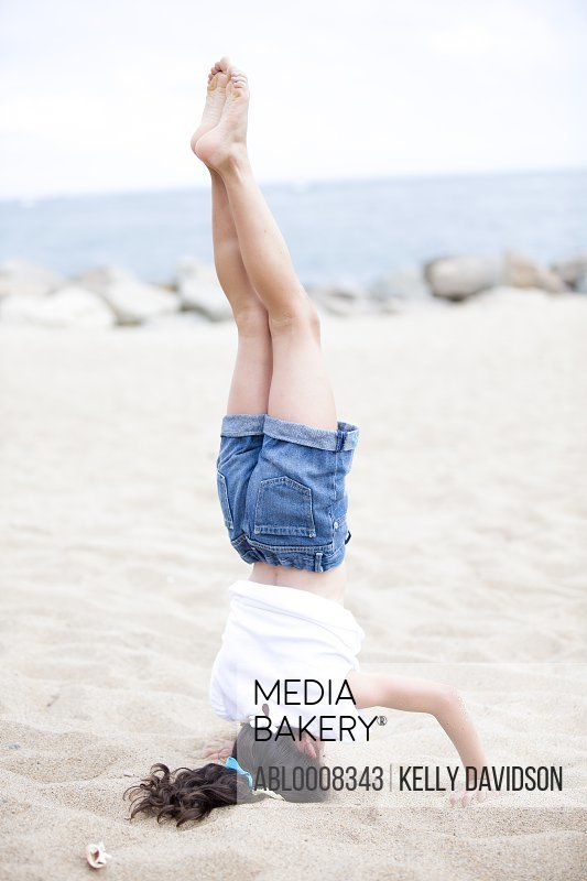 Girl Doing Headstand on Beach