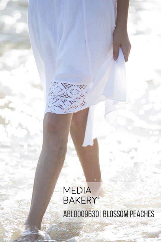 Woman in White Dress Walking in Water on Beach, Low Section