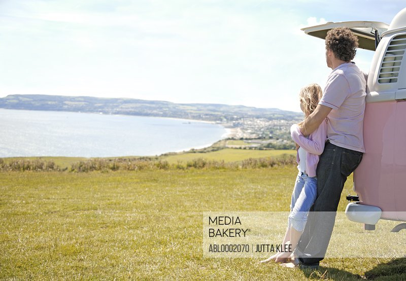 Father and Daughter Leaning on Back of Camper Van Looking at Ocean