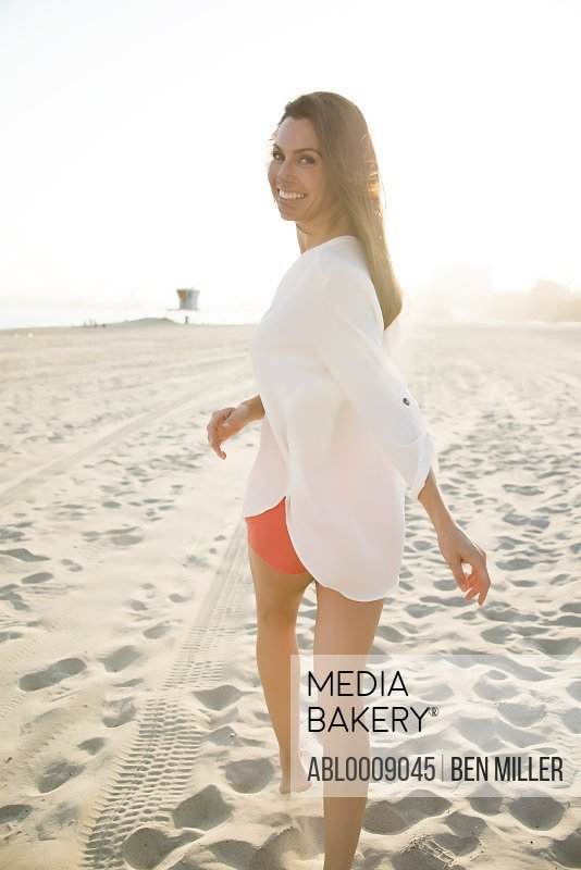 Woman Walking on Beach Looking over Shoulder