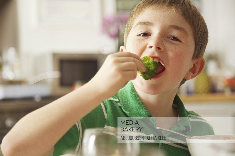Young Boy Eating Broccoli