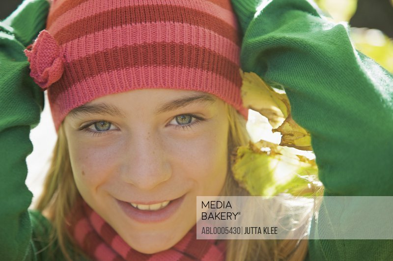 Smiling young girl with her hands on her head wearing a woolly hat