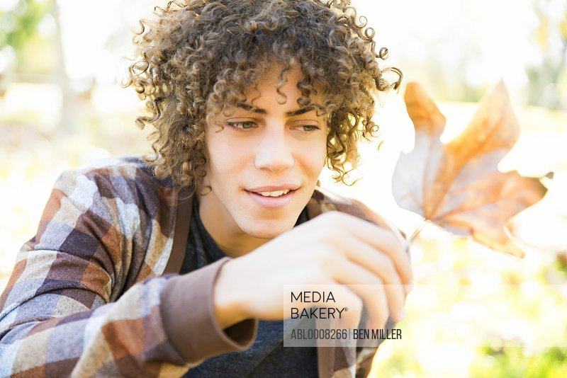 Young Man Holding Autumn Leaf