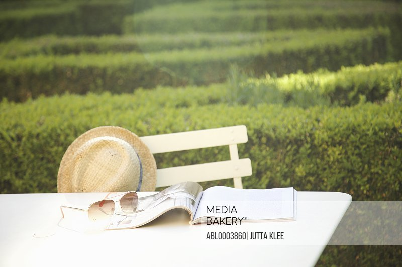 Magazine, Sunglasses and Hat on Table in Garden