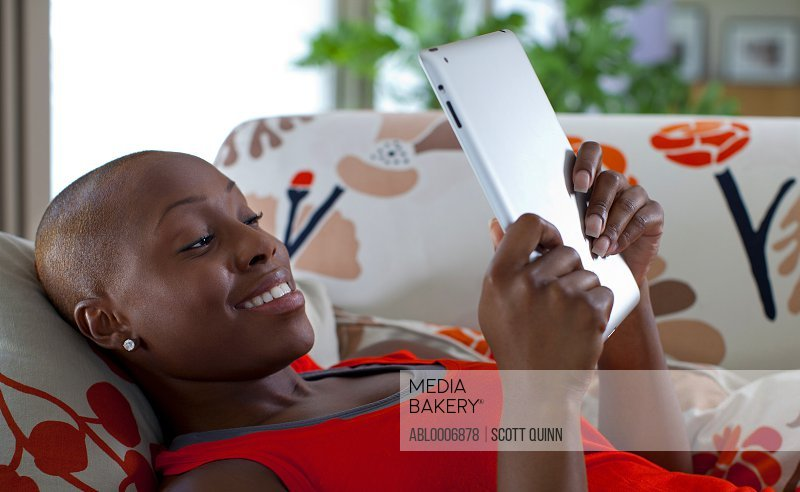 Woman Lying on Sofa Reading Electronic Book