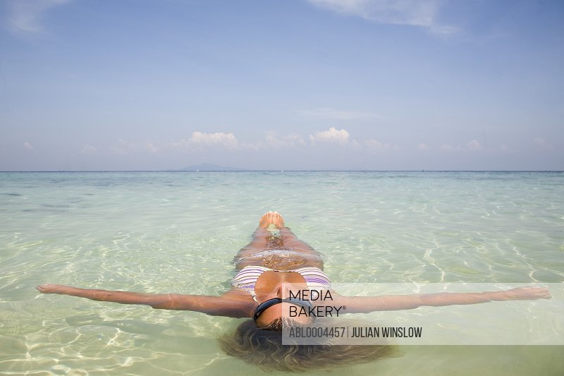 Young woman floating in crystal clear sea water with arms wide open