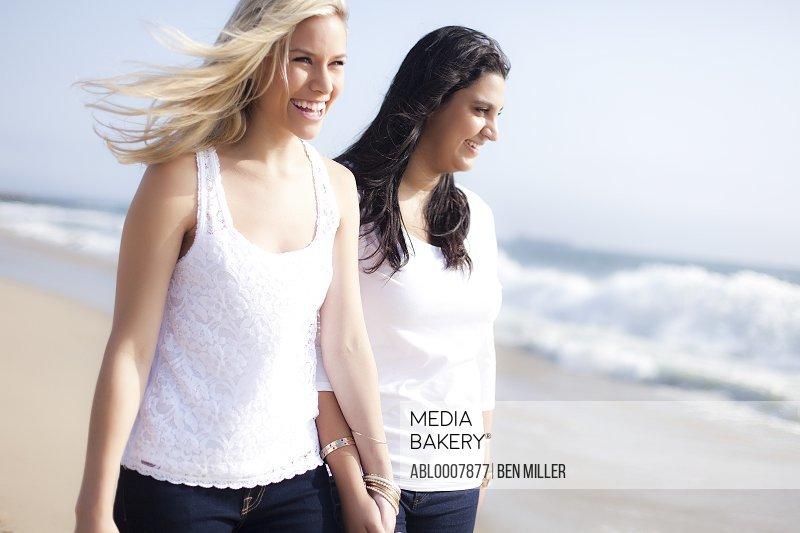 Two Smiling Women Walking on a Beach