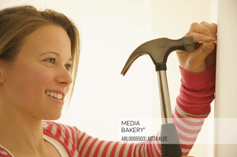 Woman hammering a nail into a wall