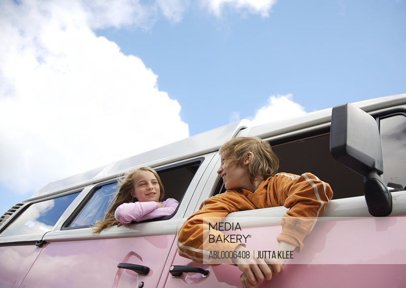 Boy and Girl Leaning out of Camper Van Window