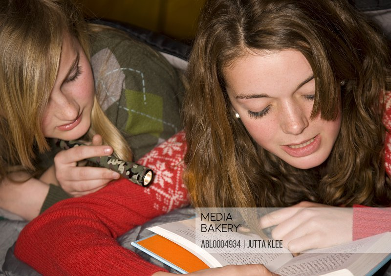 Two teenaged girls lying in a tent reading a book by torchlight