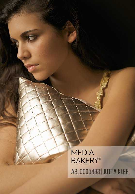 Woman hugging a gold quilted cushion