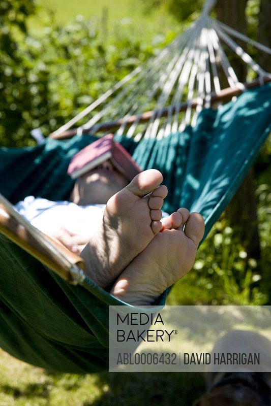 Man Sleeping on Hammock with Book over Face