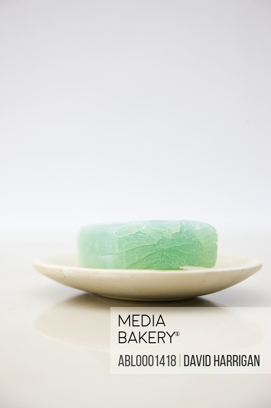 Close up of a green soap on a soap dish