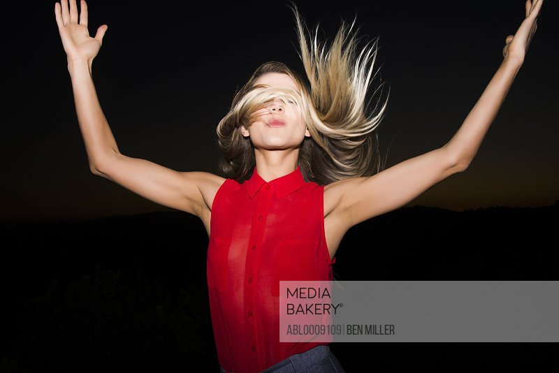 Young Woman with Arms Raised Flipping Hair