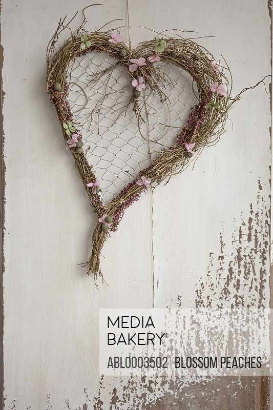 Twigs and Flowers Heart Shaped Wreath Hanging from Wall