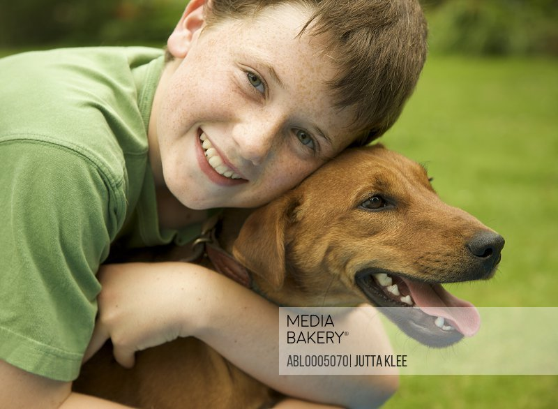 Young smiling boy embracing his dog