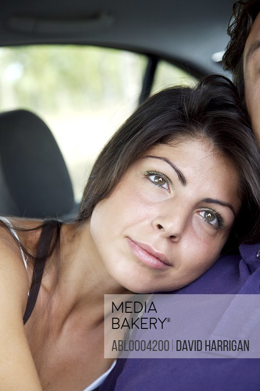 Close up of young woman leaning on man's chest looking into the distance