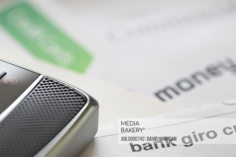 Cell phone lying on a pile of letters and financial documents