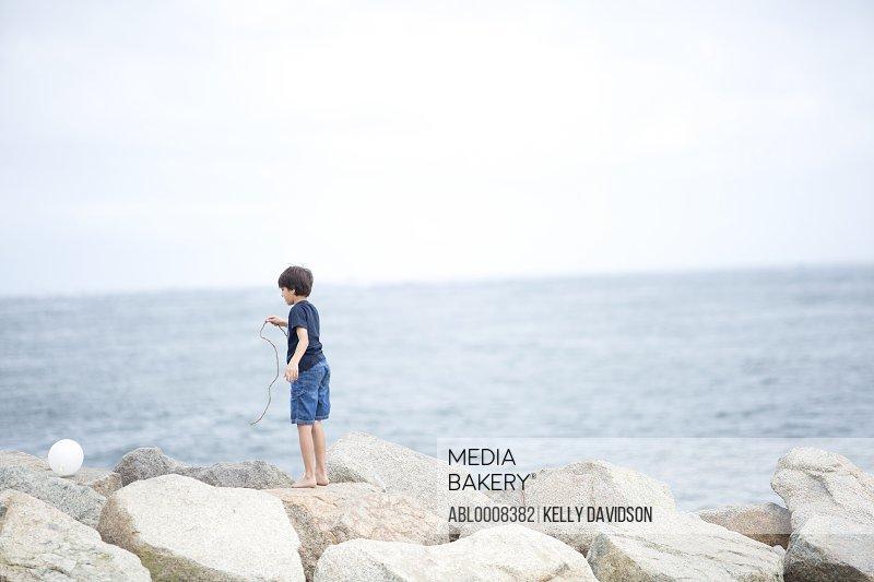 Boy on Rocks By Sea Chasing Balloon