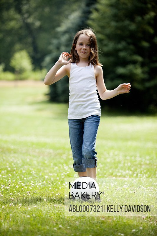Young Girl Kicking Football in Park