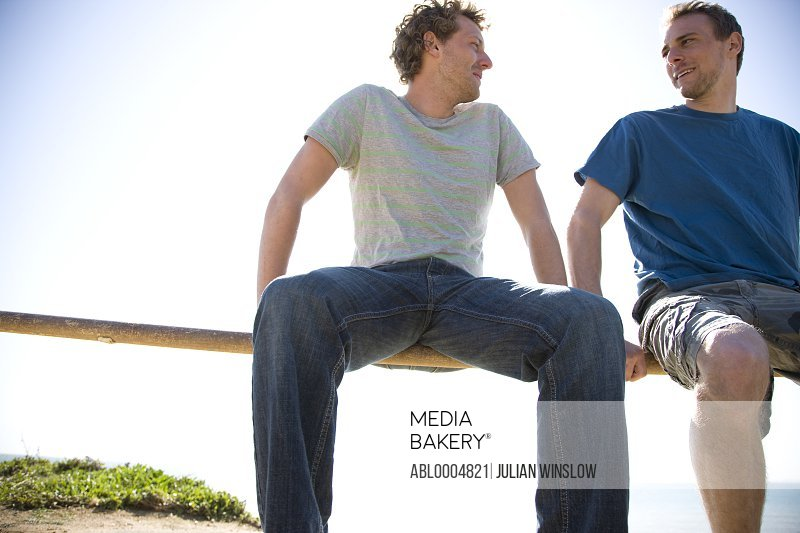 Two young men sitting on a wooden fence talking  and smiling