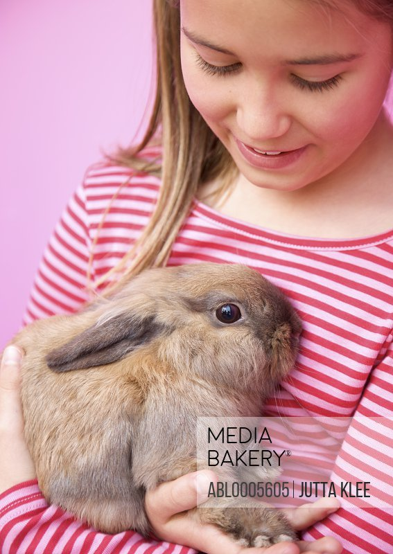 Young girl holding a rabbit