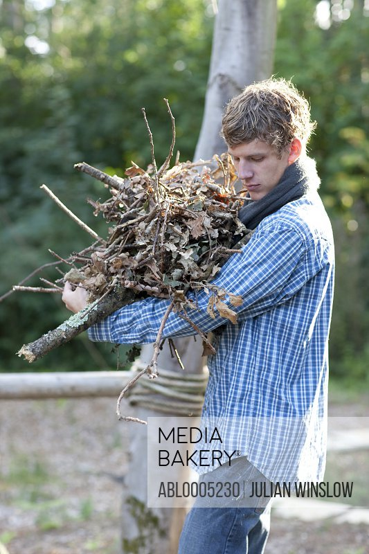 Young man carrying firewood