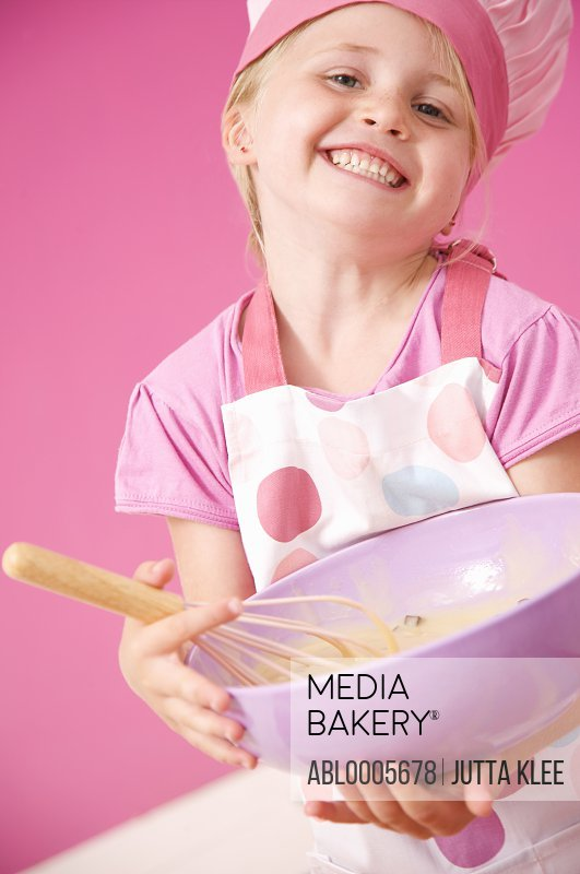 Smiling young girl holding a baking bowl and a whisk