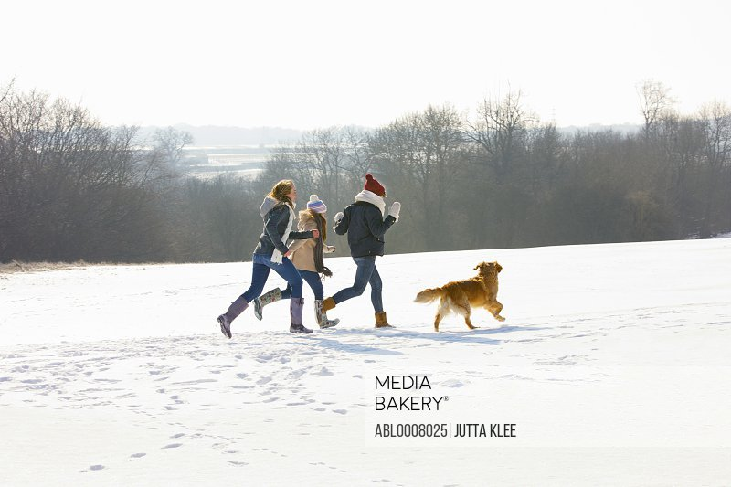 Teenage Girls and Dog Running in Snow