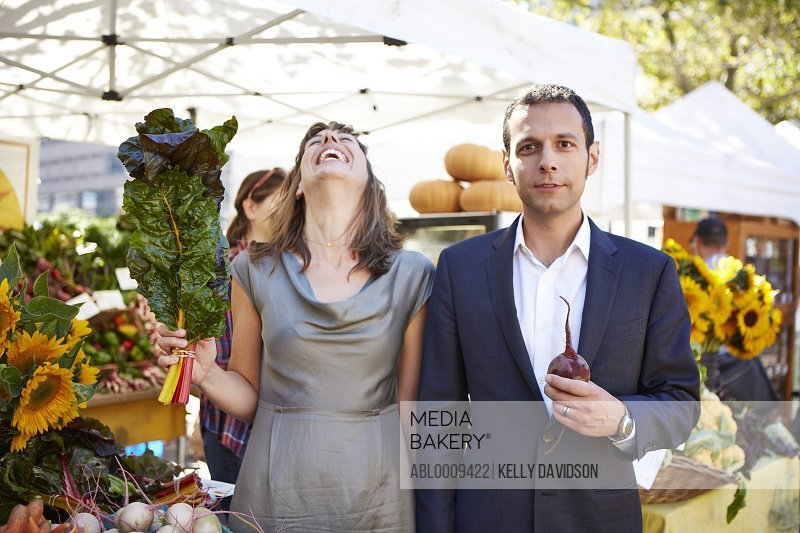 Woman Holding Swiss Chard Leaves and Man Holding Beet at Farmers Market