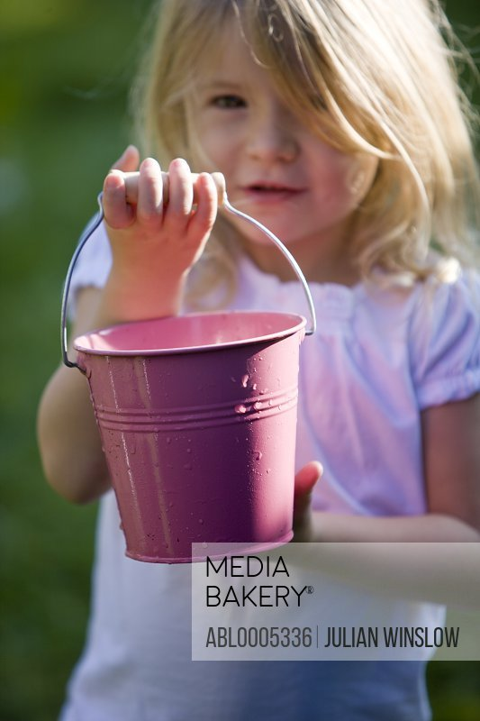 Young girl holding a pink toy bucket