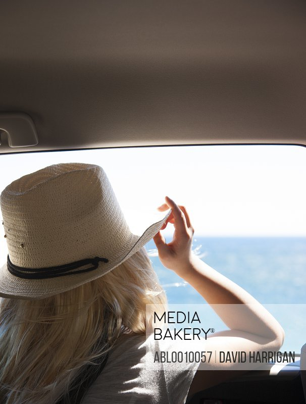 Back View of Woman Looking at the Ocean from Inside Car
