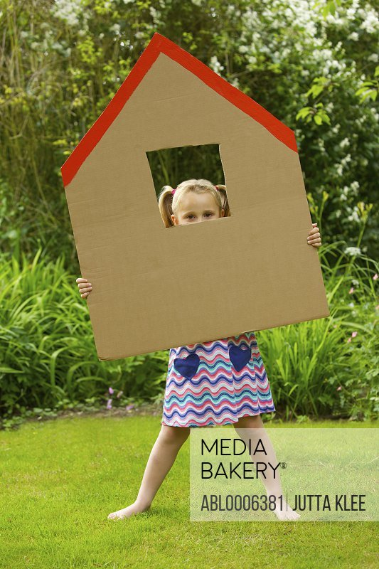 Girl Looking Out from the Window of Cardboard Cut Out in Shape of House