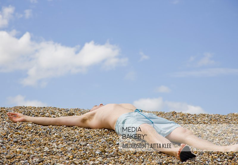 Man lying on back sunbathing on a pebble beach