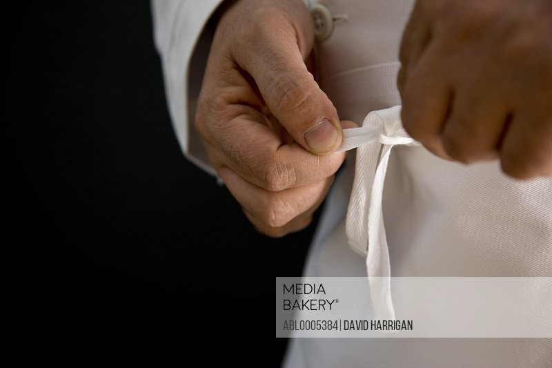 Close up of a chef hands fastening his apron