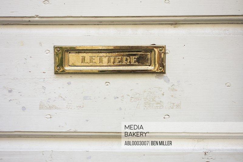 Brass Mail Slot on White Door