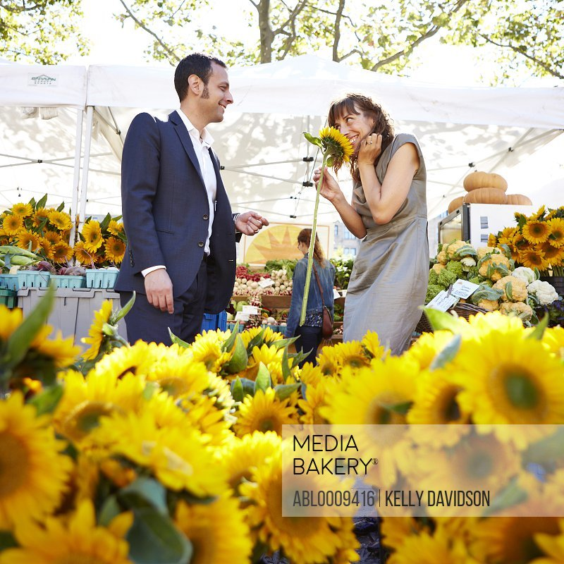 Woman Receiving Flower From Man at Farmers Market