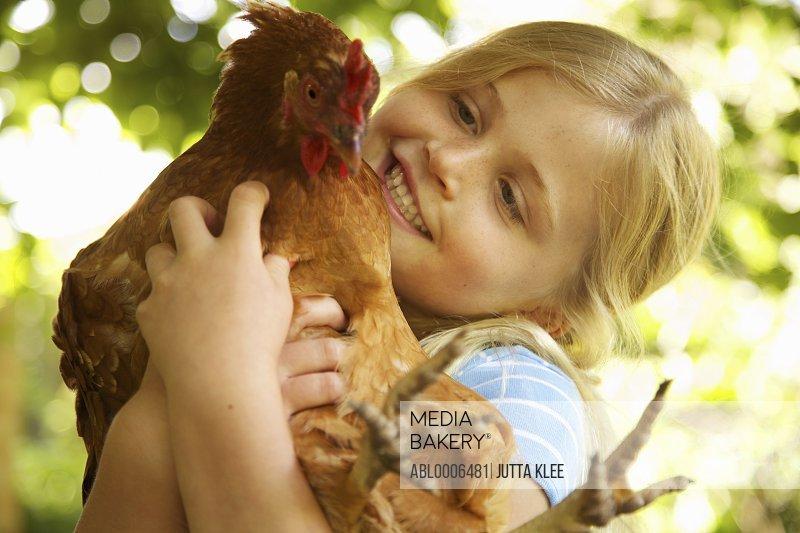 Smiling Girl Hugging Chicken