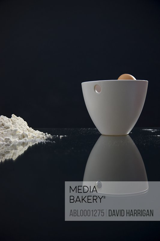 Close up of a heap of flour and a white bowl with an egg