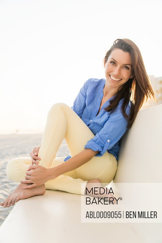 Smiling Woman Sitting on Beach Bench