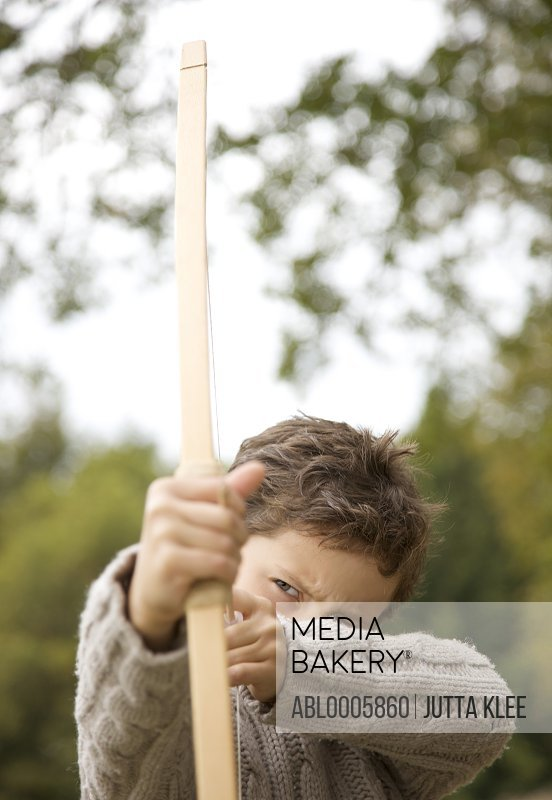 Boy aiming with a bow and arrow