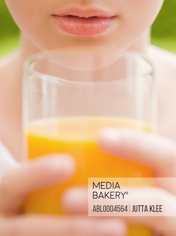 Extreme close up of young woman holding a glass of orange juice
