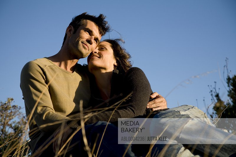 Portrait of couple embracing sitting on field