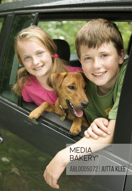 Young boy  and young girl with dog leaning out of car window