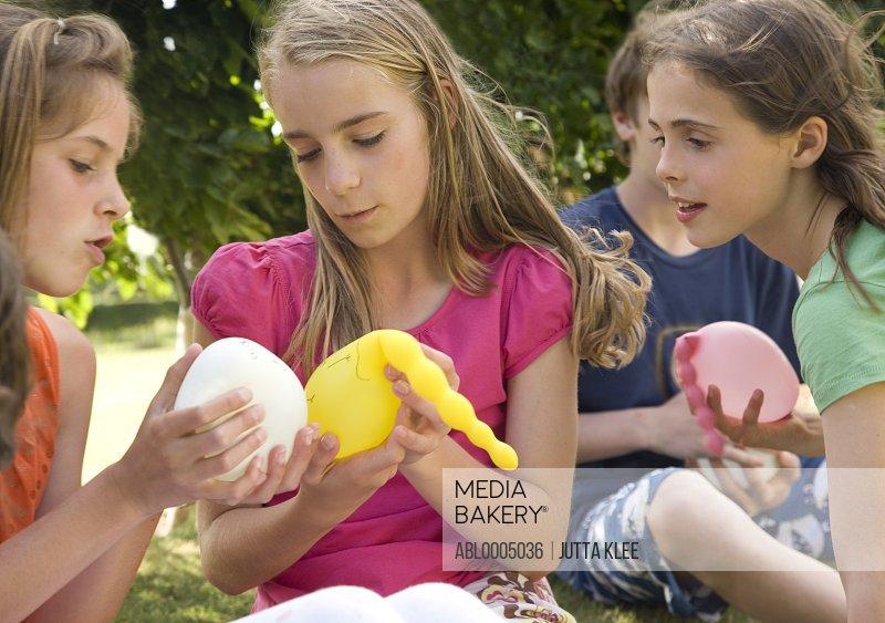 Girls holding balloons full of water
