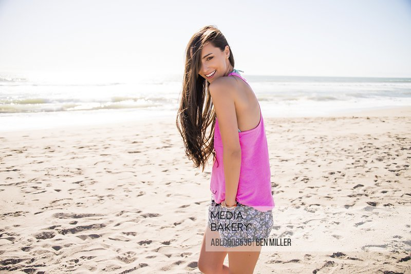 Smiling Young Woman on Beach with Hands in Pockets