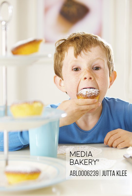 Yong boy biting a cupcake