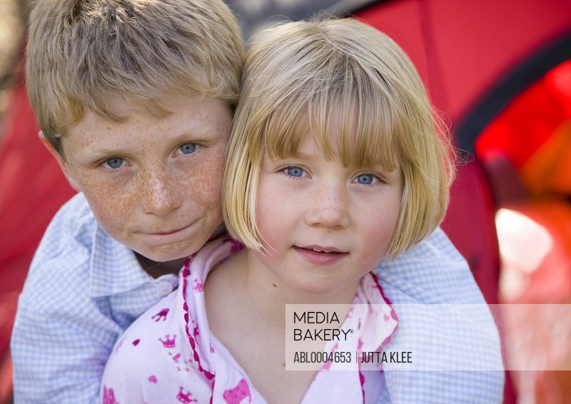 Close up of boy and girl embracing outside tent